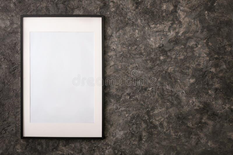 Marco en blanco de la foto que cuelga en la pared oscura fotos de archivo libres de regalías