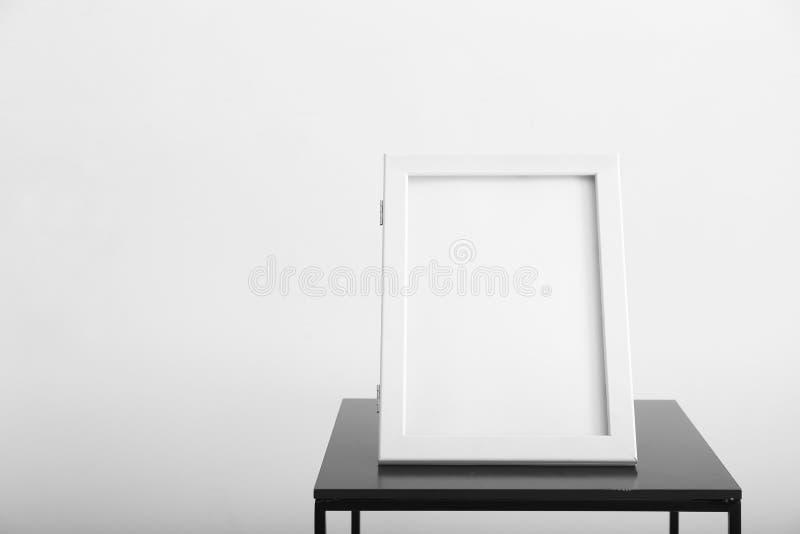 Marco en blanco de la foto en la tabla contra la pared blanca fotografía de archivo