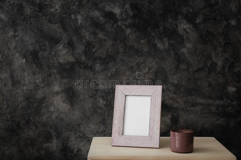 Marco en blanco de la foto en la tabla contra la pared oscura fotografía de archivo