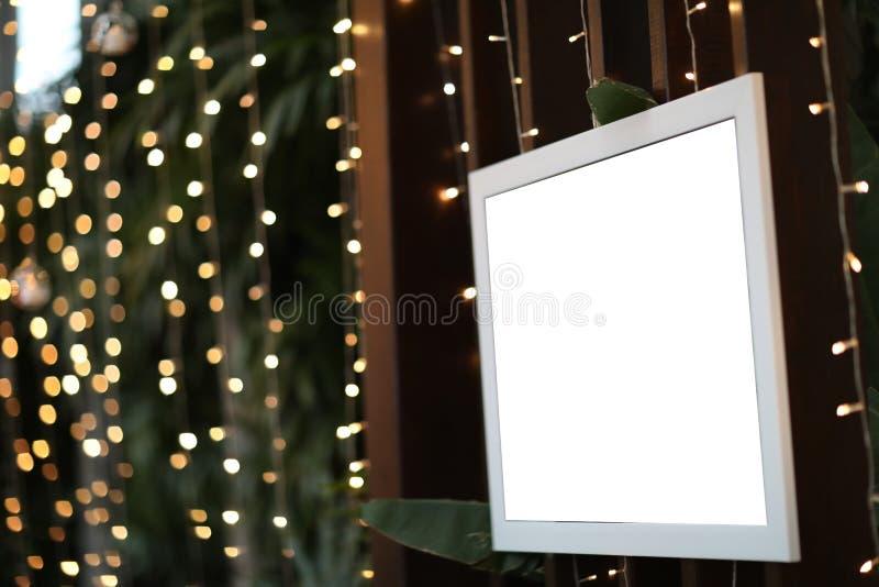 Marco en blanco vacío de la foto en fondo defocused adornado la Navidad foto de archivo libre de regalías