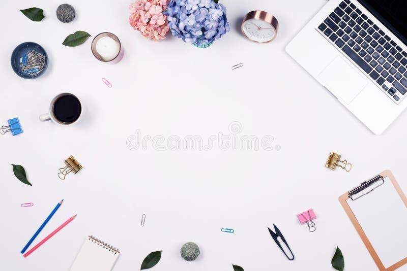 Marco femenino del espacio de trabajo del escritorio con el arreglo de las hortensias del ramo, ordenador portátil, tablero, cuad imagen de archivo
