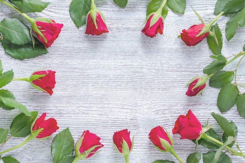 Marco floral con las rosas rojas y las hojas verdes en el fondo de madera, visión superior imagenes de archivo