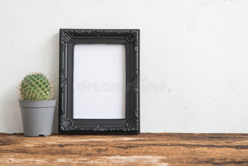 Marco negro de la foto en la tabla de madera vieja con el cactus sobre la estafa blanca fotografía de archivo libre de regalías