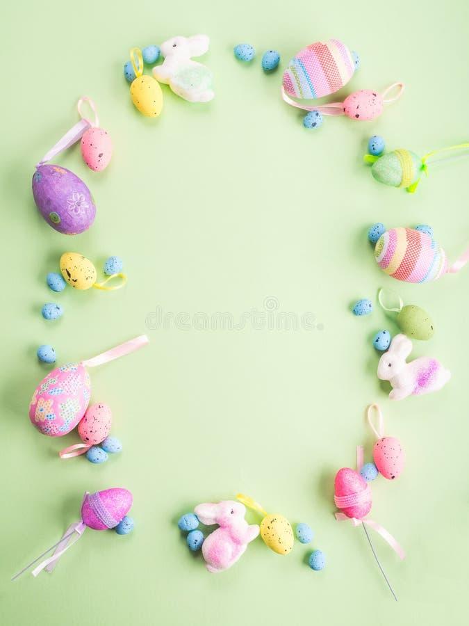 Marco puesto plano de la decoraci?n colorida de Pascua en pastel verde imagenes de archivo