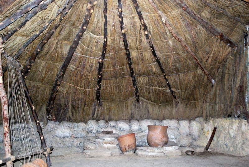 Marco que teje material de la Edad de Piedra y potes de cerámica dentro de una choza en el museo del palacio de Mondragon, Ronda, fotografía de archivo libre de regalías