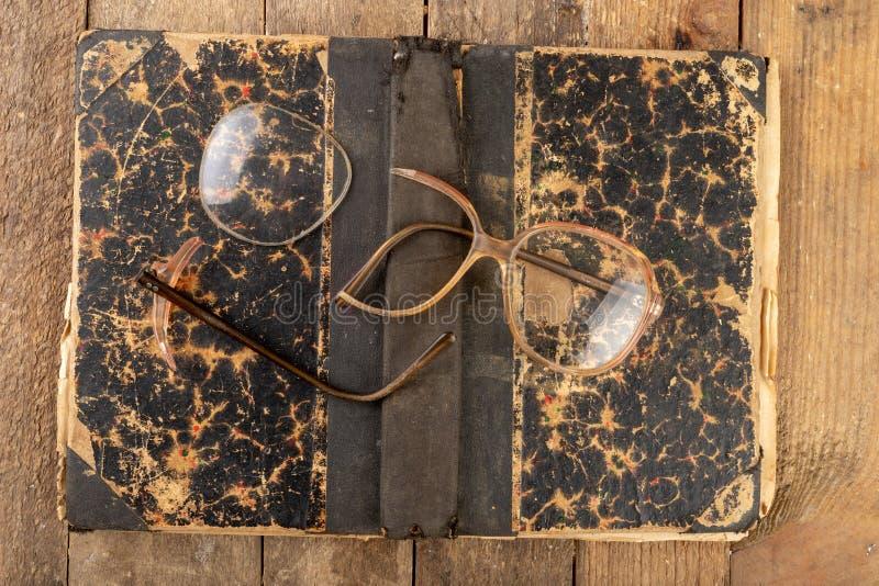 Marco quebrado de los vidrios Libro viejo y vidrios fotografía de archivo