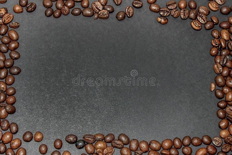 Marco rectangular hecho de los granos de café marrones fritos en un fondo gris oscuro imagen de archivo libre de regalías