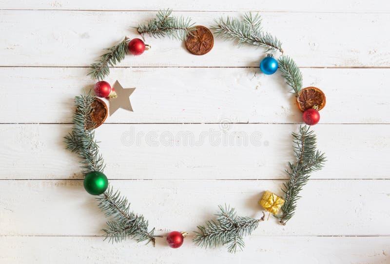Marco redondo de la Navidad El abeto ramifica, poinsetia de la Navidad en fondo blanco de madera Endecha plana, visión superior fotografía de archivo libre de regalías