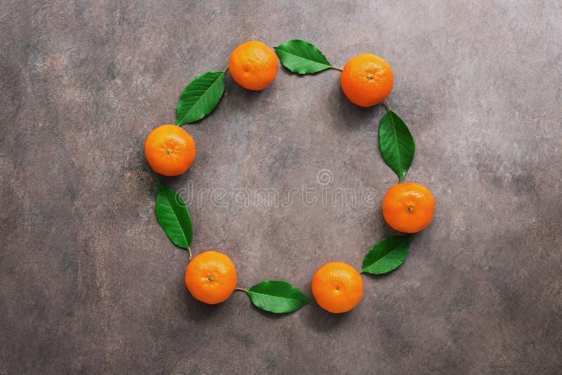 Marco redondo de las mandarinas y de las hojas verdes en un fondo rústico oscuro Visi?n superior, endecha plana, espacio de la co foto de archivo