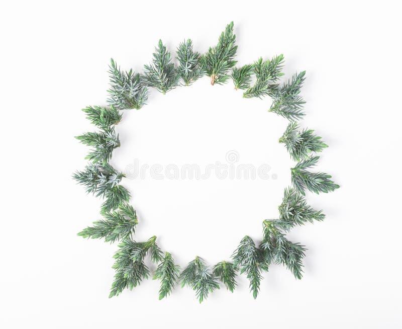 Marco redondo hecho de las ramas del enebro aisladas en el fondo blanco Endecha plana Compo de la Navidad o del Año Nuevo imagenes de archivo