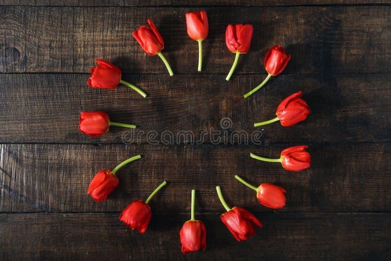 Marco redondo hecho de tulipanes rojos en fondo de madera oscuro imagenes de archivo