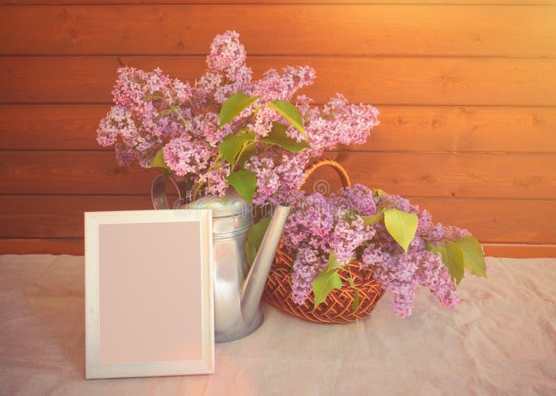 Marco, regadera y cesta blancos con las ramas de la flor de la lila en la tabla imagenes de archivo