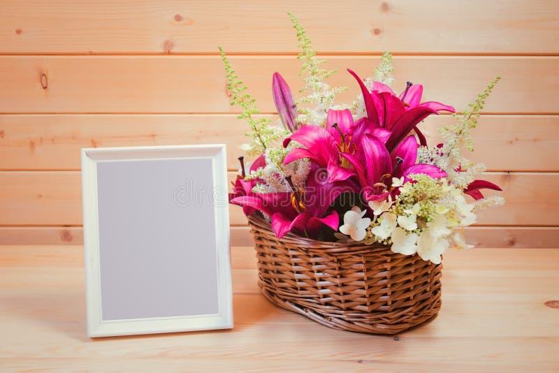 Marco vacío blanco y cesta de mimbre con los lirios púrpuras y las flores blancas del astilbe y de la hortensia en la tabla de ma imagen de archivo libre de regalías