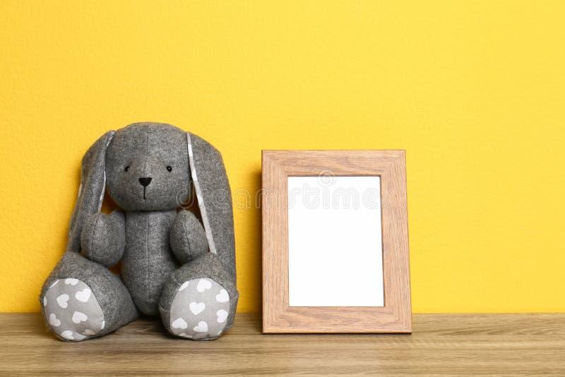 Marco vacío de la foto y y conejo suave en la tabla contra el fondo amarillo, espacio para el texto Interior de la habitaci?n del imagen de archivo libre de regalías