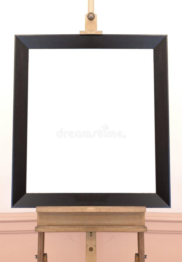 Marco vacío en blanco en el caballete de la pintura, fondo imagenes de archivo