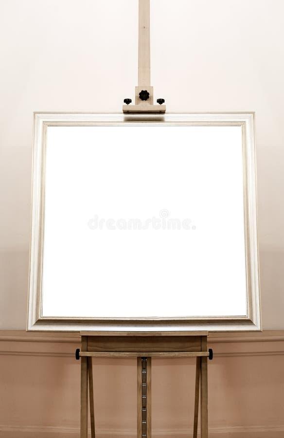 Marco vacío en blanco en el caballete de la pintura, fondo imagen de archivo