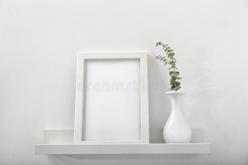 Marco y florero en blanco de la foto en estante imagen de archivo libre de regalías