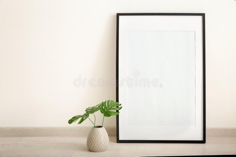 Marco y florero en blanco de la foto en piso cerca de la pared blanca foto de archivo