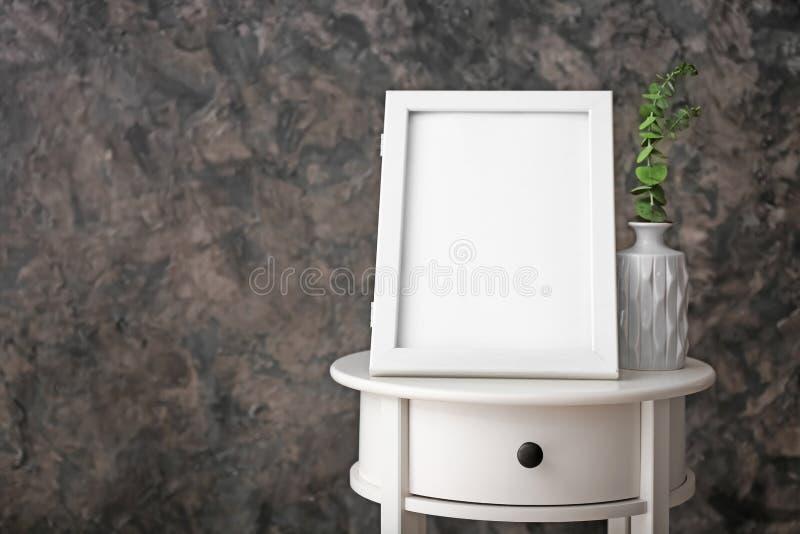 Marco y florero en blanco de la foto en la tabla contra la pared oscura imágenes de archivo libres de regalías