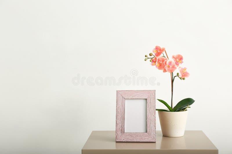 Marco y houseplant en blanco de la foto en la tabla contra la pared blanca imagenes de archivo