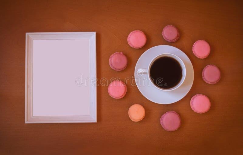Marco y taza de café blancos con los macarrones coloridos en fondo de madera foto de archivo