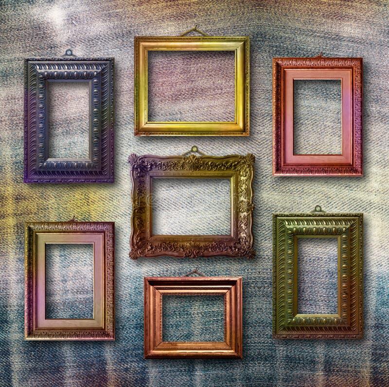 Marcos de madera dorados para las imágenes en fondo de los vaqueros imagen de archivo libre de regalías