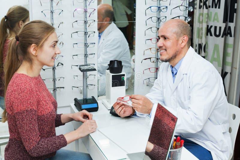 Marcos de ofrecimiento de los vidrios del óptico masculino mayor positivo a la mujer imagenes de archivo