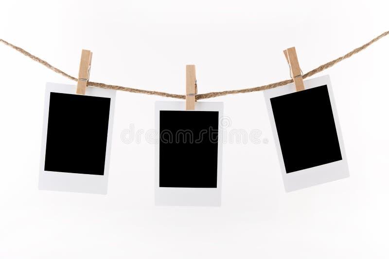 Marcos polaroid de la foto en cuerda imagen de archivo