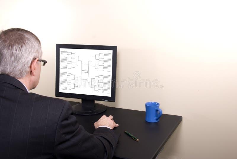 Marcowego obłąkania Biznesowy mężczyzna Patrzeje wspornika na monitorze w kostiumu zdjęcie stock