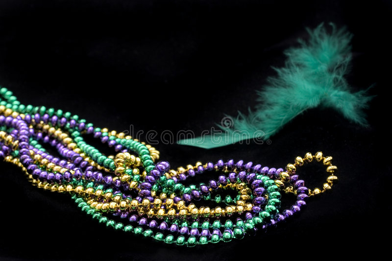 Mardi gras beads with green feather. On black background stock photos
