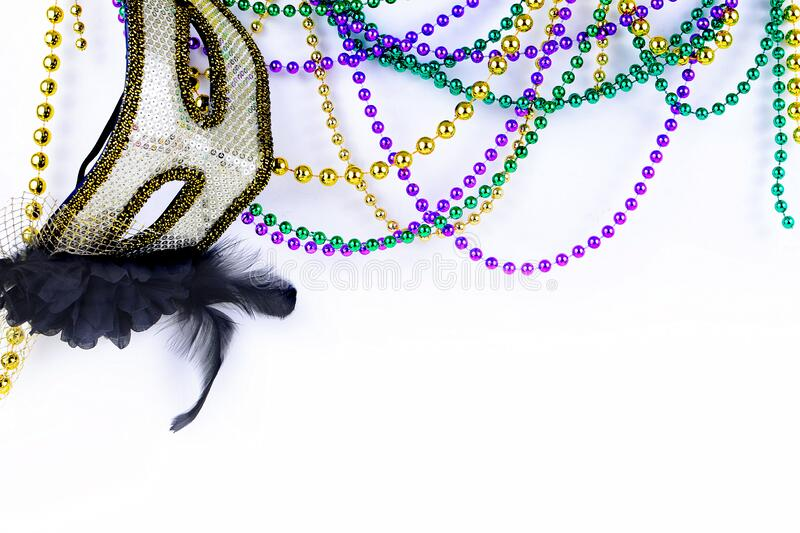 Mardi Gras beads in green, gold and purple hanging, draped in front of a white background royalty free stock photography