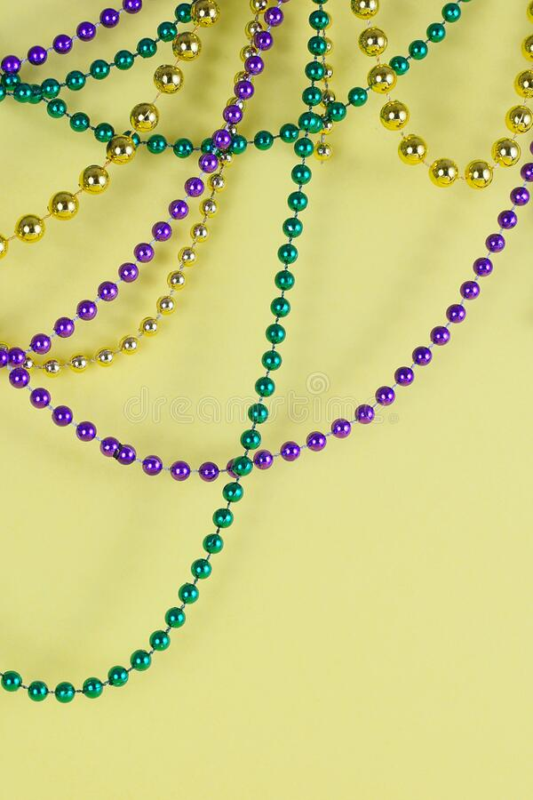 Mardi Gras beads in green, gold and purple hanging, draped in front of a yellow background. stock images