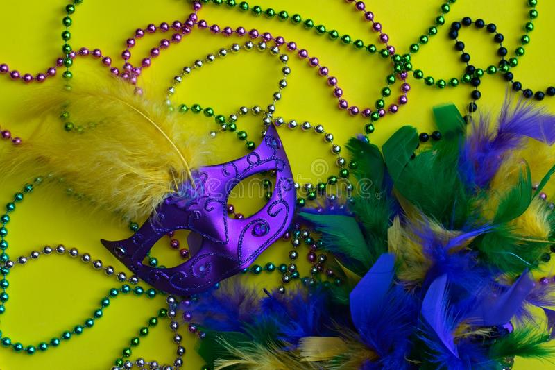 Mardi Gras beads, mask and boa. Yellow Mardi Gras background with mask, beads and feather boa. The Mardi Gras carnival is held in several US states but is best royalty free stock photos