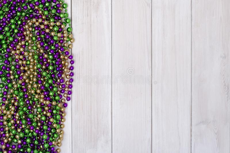 Mardi Gras beads on white wooden backgound royalty free stock photography