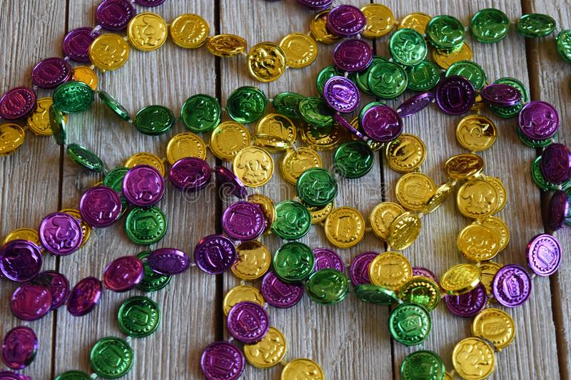 Mardi Gras beads on a wood background royalty free stock photos