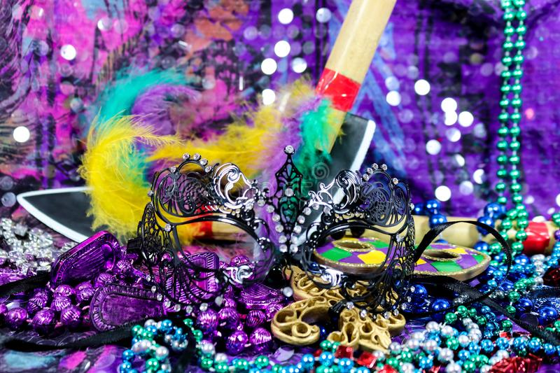 Mardi Gras Carnaval background with black filigree mask assorted beads and feathered bamboo spears - selecive focus with bokeh royalty free stock images