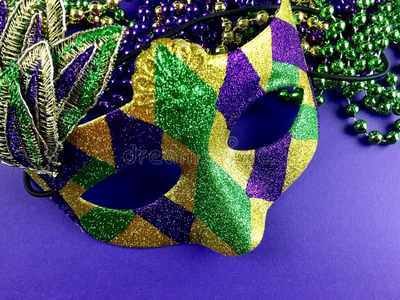 Mardi gras mask and beads. Close up of a festive mardi gras mask and beads on a purple surface stock photography