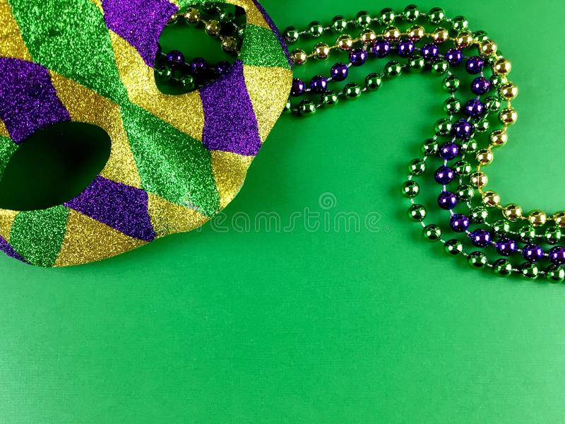 Mardi Gras. Mask and beads on a green background royalty free stock photos