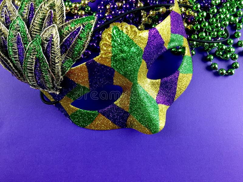 Mardi Gras. Mask and beads on a purple background stock images