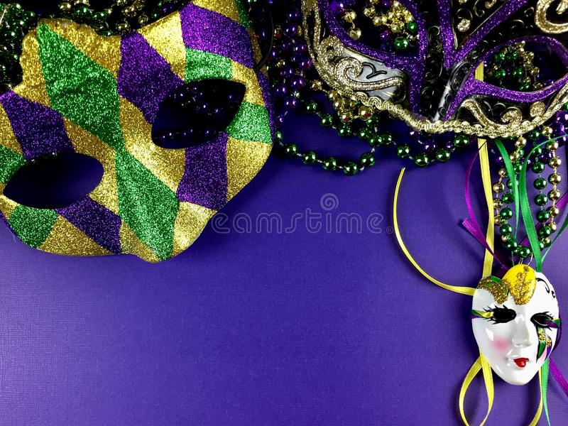 Mardi Gras. Mask and beads on a purple background stock photos