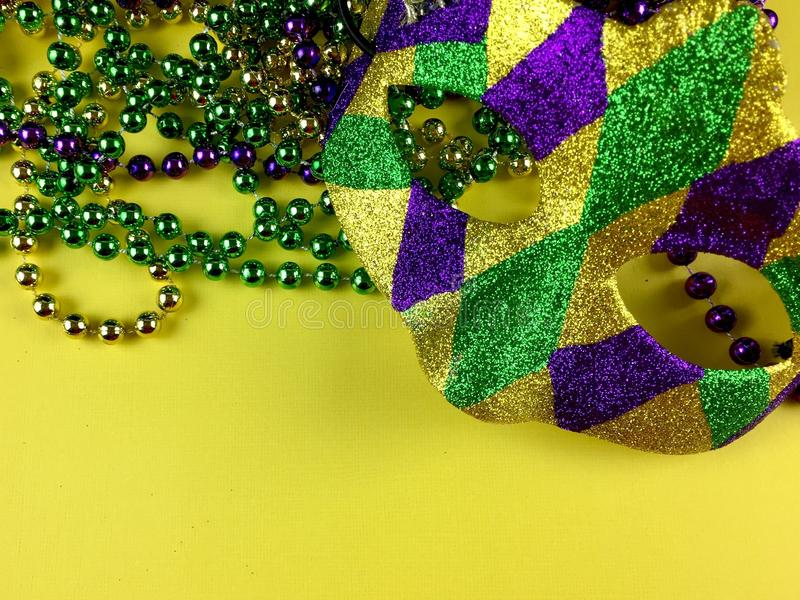 Mardi Gras. Mask and beads on a yellow background royalty free stock photo