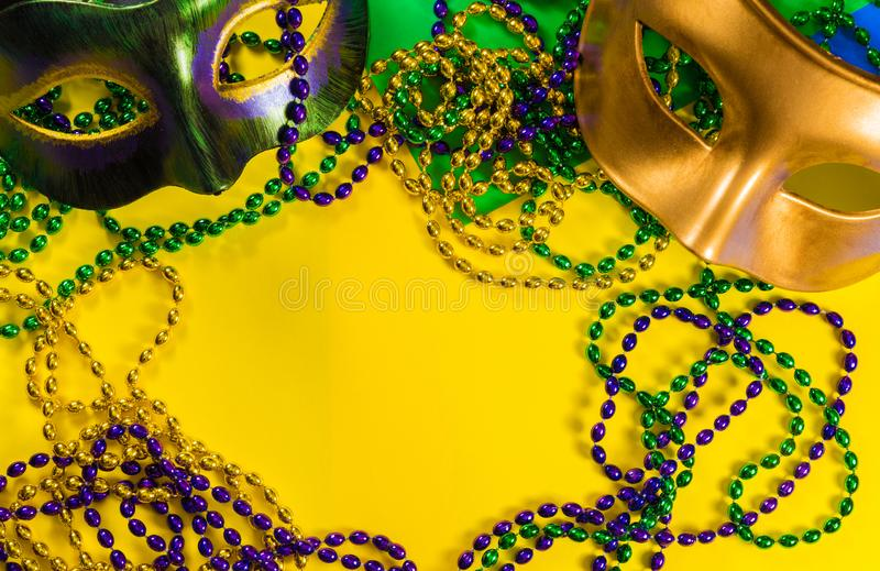 Mardi Gras mask with beads on a yellow background. Two Mardi Gras mask with colorful beads on a yellow background royalty free stock image