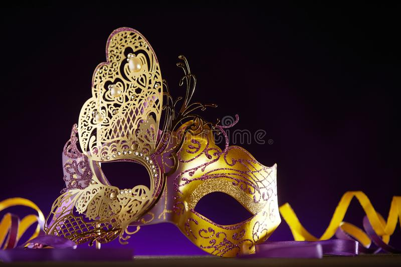 Mardi gras mask lying on the ground next to ribbon. Reflective mardi gras mask lying on the ground next to multicolored spiraling ribbon in front of black stock photos