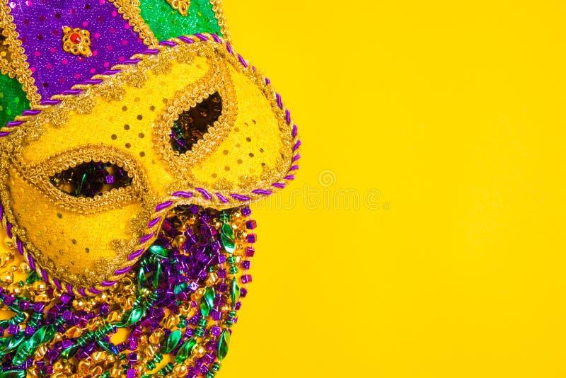 Mardi Gras Mask on yellow Background. A venetian, mardi gras mask or disguise on a yellow background stock image