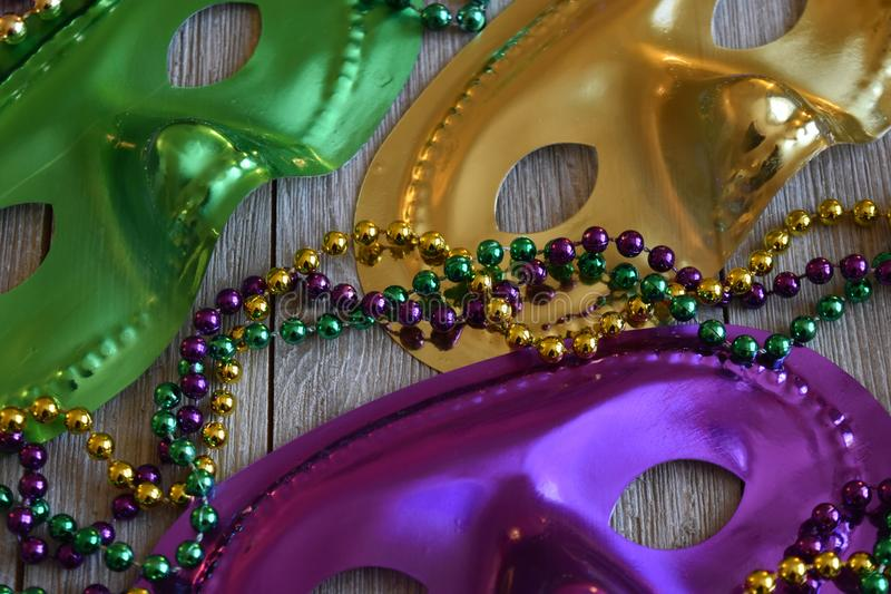 Mardi Gras masks with beads on a wood background stock images
