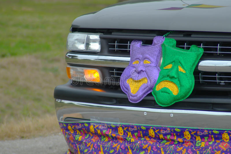 Mardi Gras Parade. The front of a pickup truck is decorated with tragedy/comedy masks and a Mardi Gras banner during a celebration parade in Lafayette, Louisiana stock photography