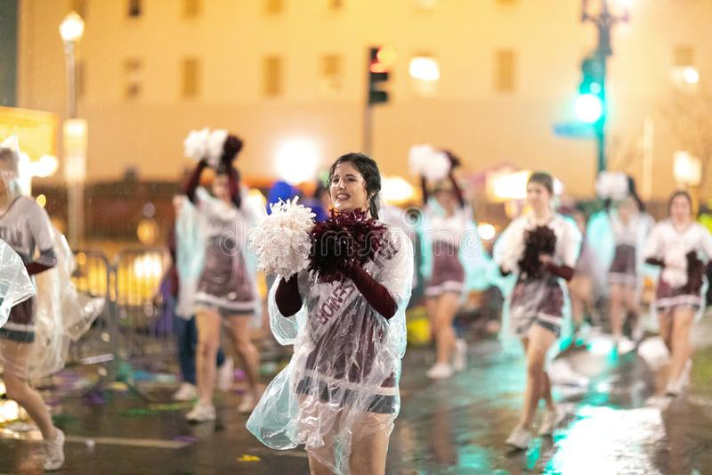 Mardi Gras Parade New Orleans. New Orleans, Louisiana, USA - February 23, 2019: Mardi Gras Parade, Cheerleaders under heavy rain performing at the Mardi Gras stock image