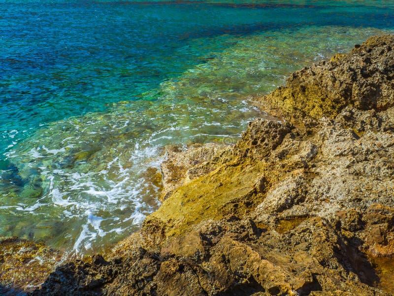 Mare blu surreale e riva rocciosa gialla immagini stock