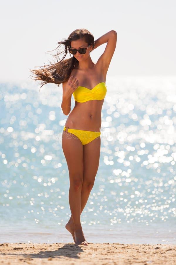 Mare castana del costume da bagno di giallo della donna immagini stock libere da diritti