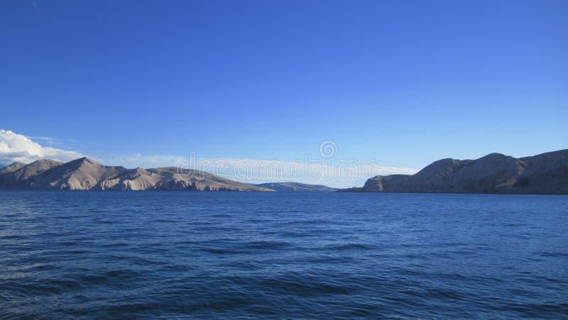 Mare, cielo e montagne blu fotografie stock libere da diritti